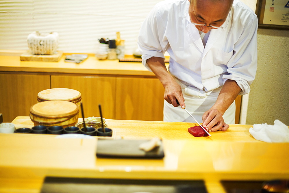 A chef working in a small commercial kitchen, an itamae or master chef slicing fish with a large knife for making sushi, Japan - 1174-4269