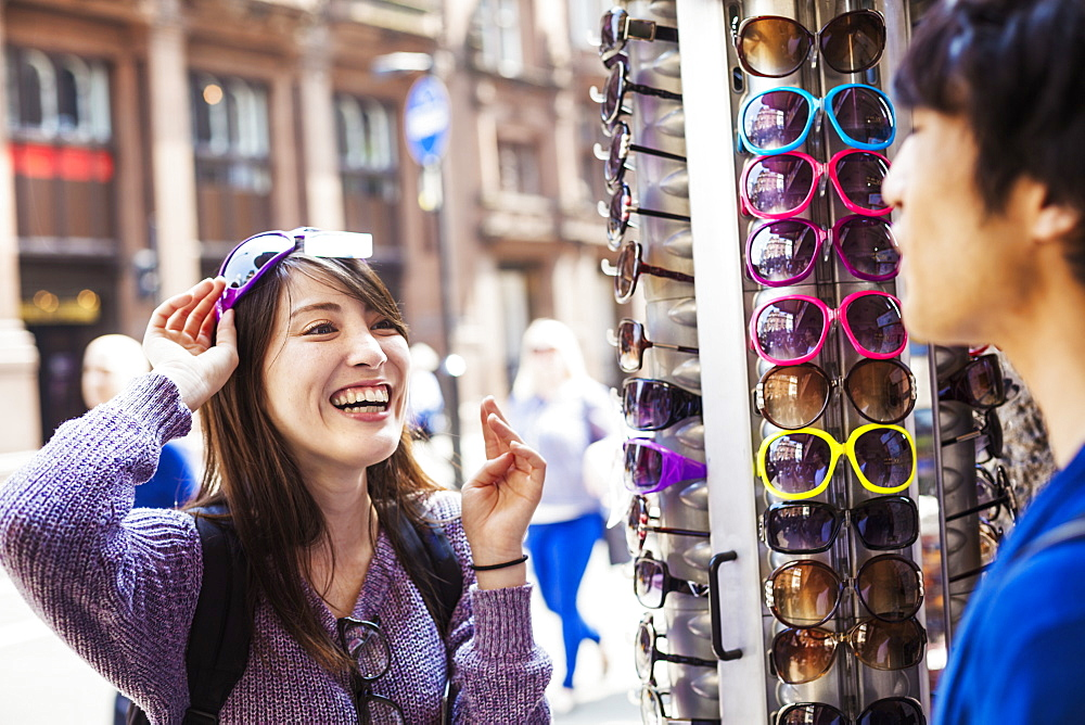 A Japanese woman trying on sunglasses in London, a summer tourist visitor, England