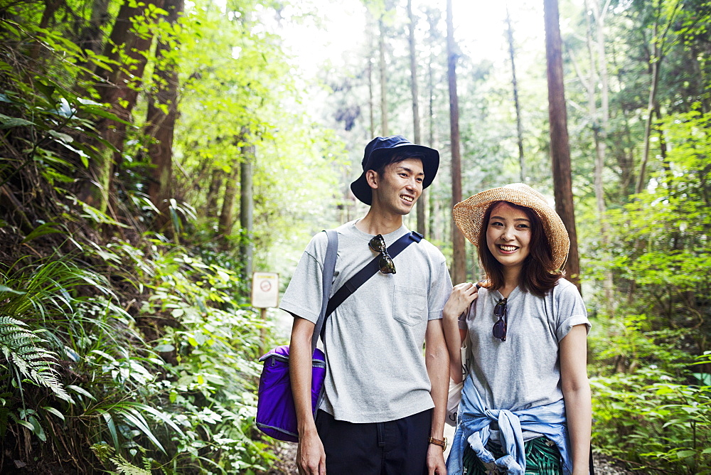 Smiling young woman and man standing in a forest, Japan