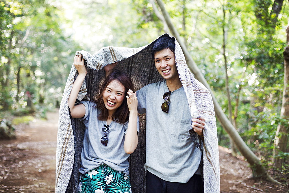 Young woman and man standing in a forest, holding a blanket over their heads, Japan