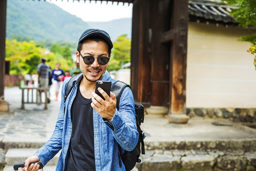 A man in sunglasses looking at his smart phone, Japan