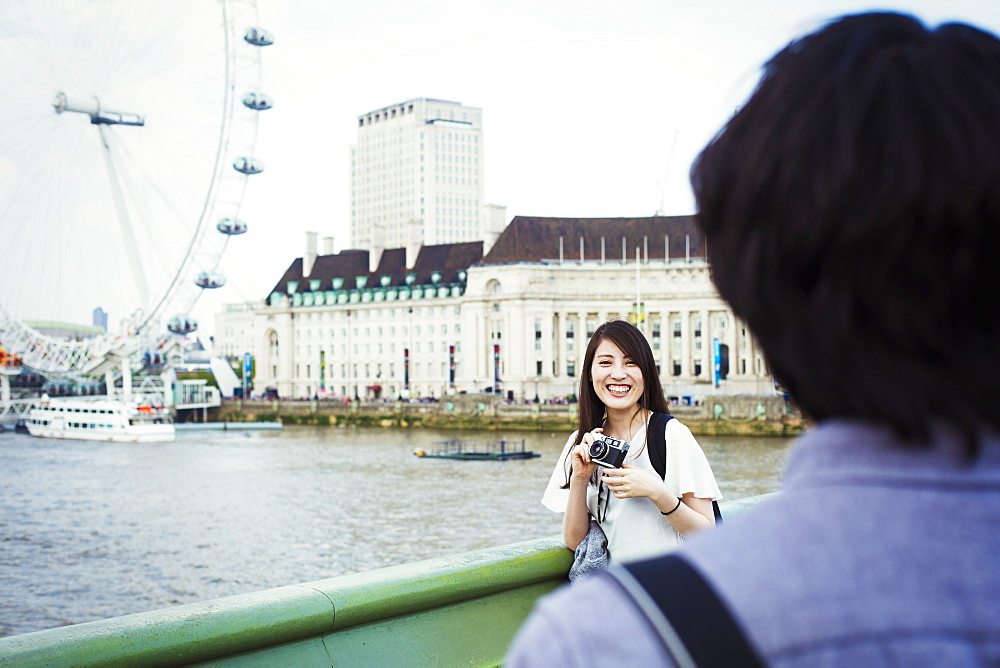 Young Japanese man and woman enjoying a day out in London, standing by the River Thames, London Eye in the background, United Kingdom