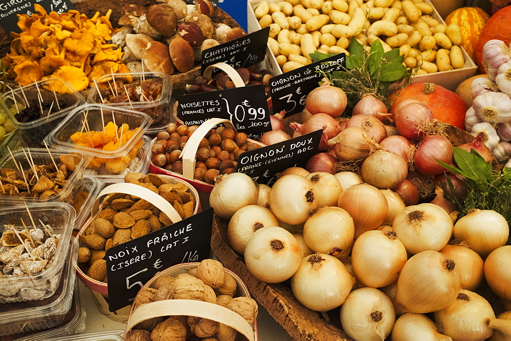 A market stall with display of fresh vegetables, onions, potatoes, walnuts and mushrooms, France