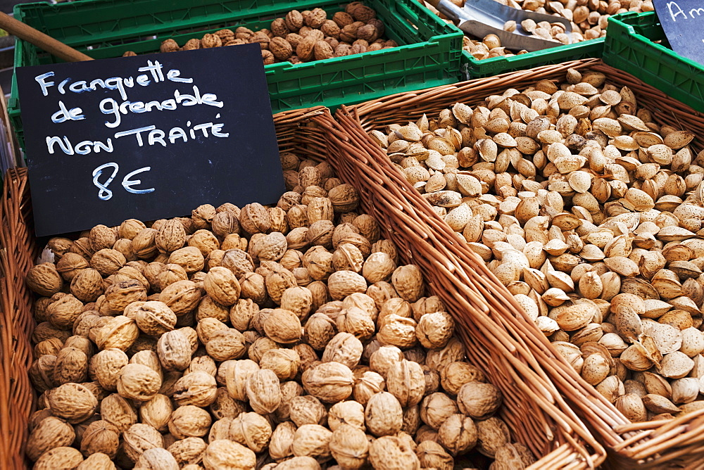 A market stall, fresh produce for sale. Baskets of walnuts and a price sign, France
