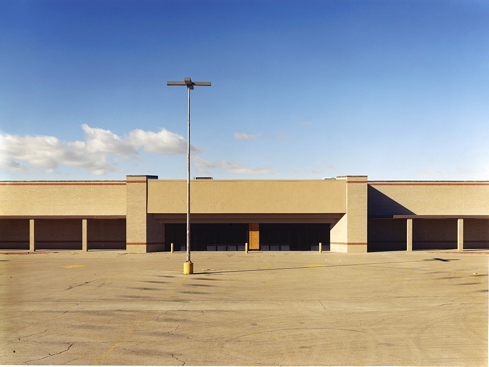 A building exterior, a single storey building with a large forecourt, carpark, USA