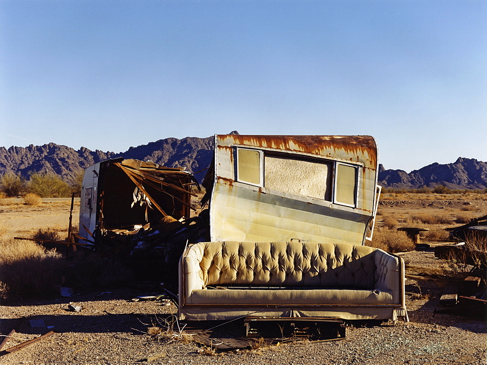 A ruined caravan, with rusting roof, a shelter, and a sofa, USA