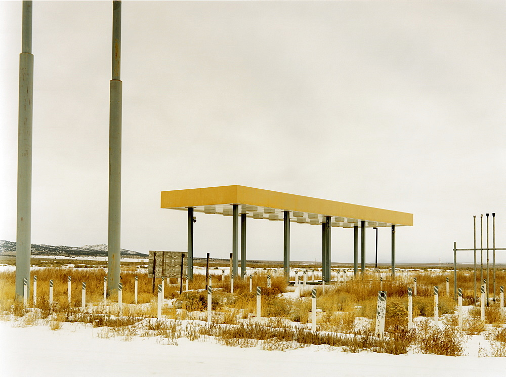 An abandoned gas station, petrol station in the middle of nowhere, plants growing over the forecourt, USA