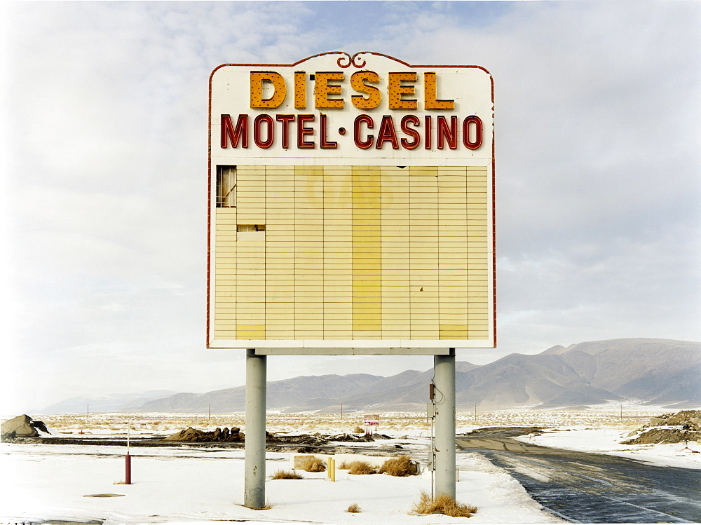 A large roadside sign in a flat landscape with light snow, Mountain range, Diesel and Motel Casino, USA