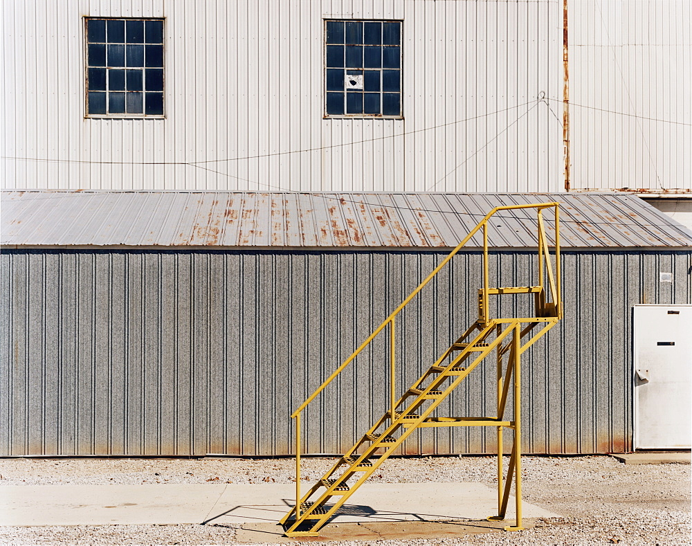 A ladder beside an industrial unit, with corrugated iron walls, USA