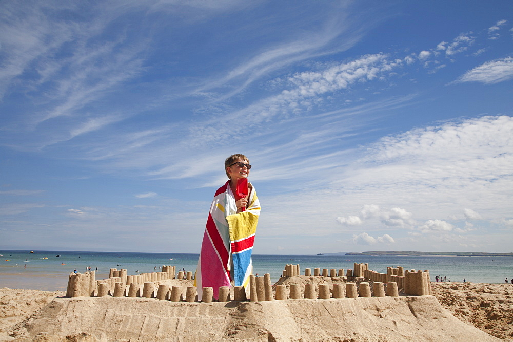 A boy standing beside a sandcastle, on top of a mound of sand. Beach, England