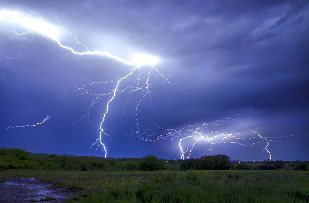A lightning storm over a landscape. Forks of lightening emerging from clouds.