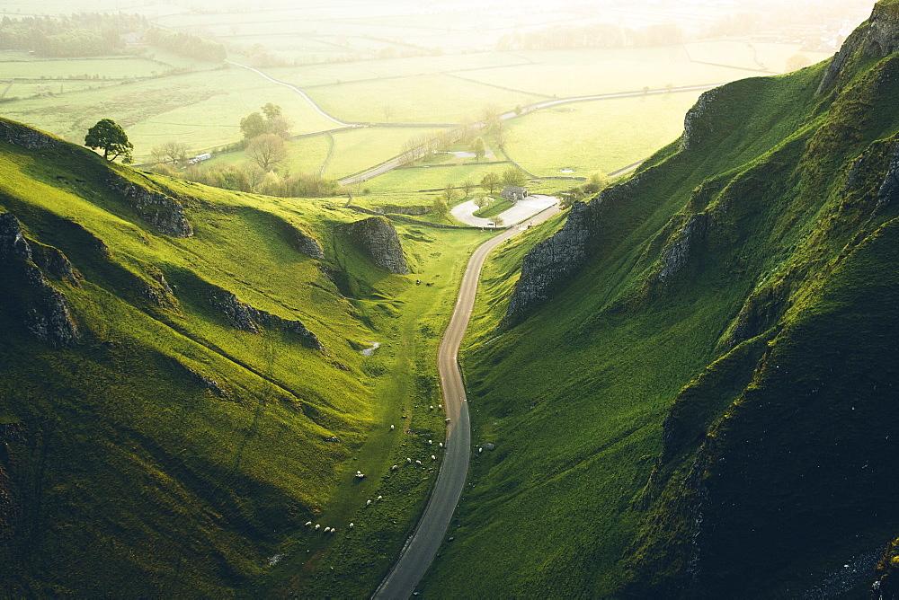 Aerial view of a road cutting through lush green mountains.