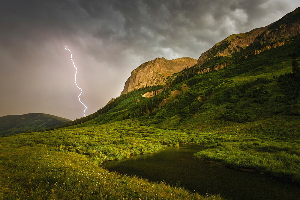 A lightning storm over river running through a mountainous valley. Fork of lightening emerging from clouds.