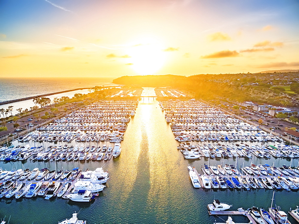 High angle view of yachts in a marina by the ocean at sunset.