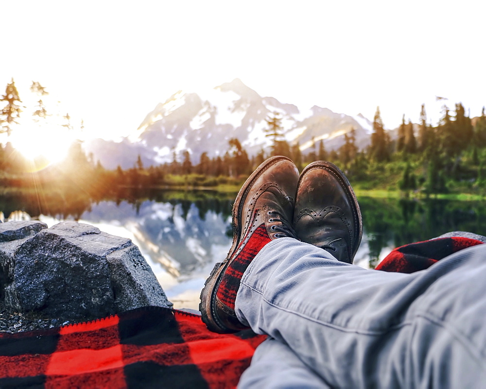 A person lying on a rug, in jeans and boots, looking at the sunset and the mountain view.