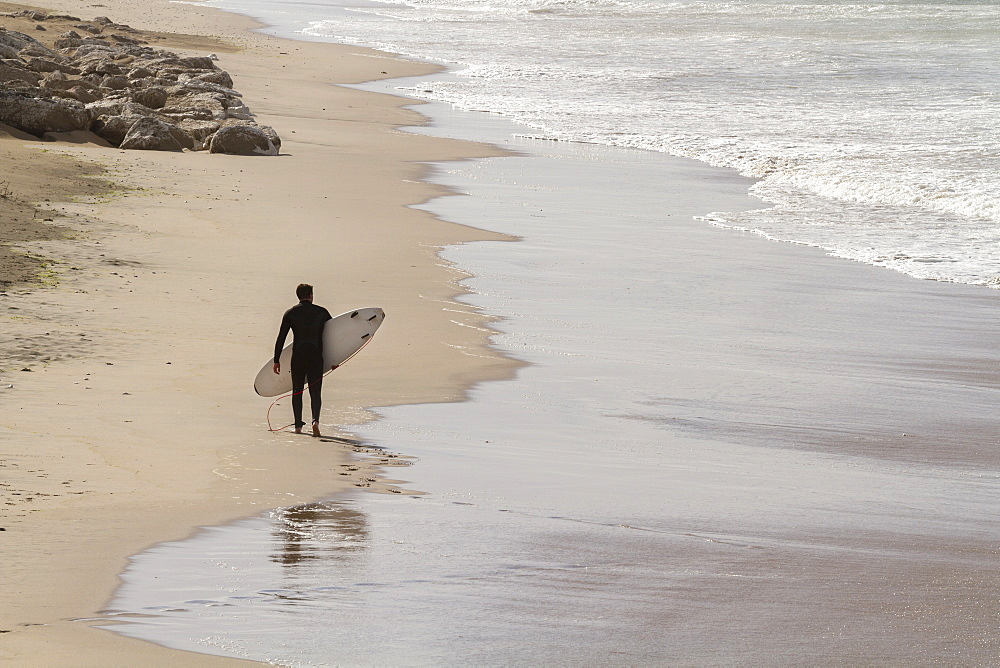 View from above of a surfer walking along a deserted beach carrying a surfboard.