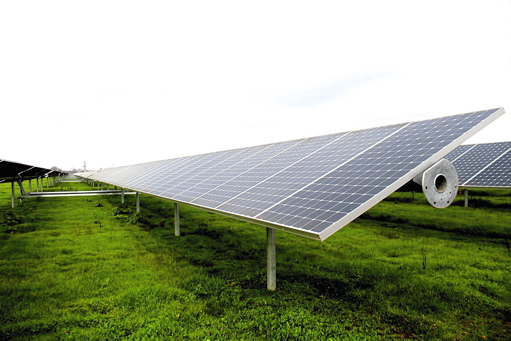 An array of photovoltaic solar panels in a field.