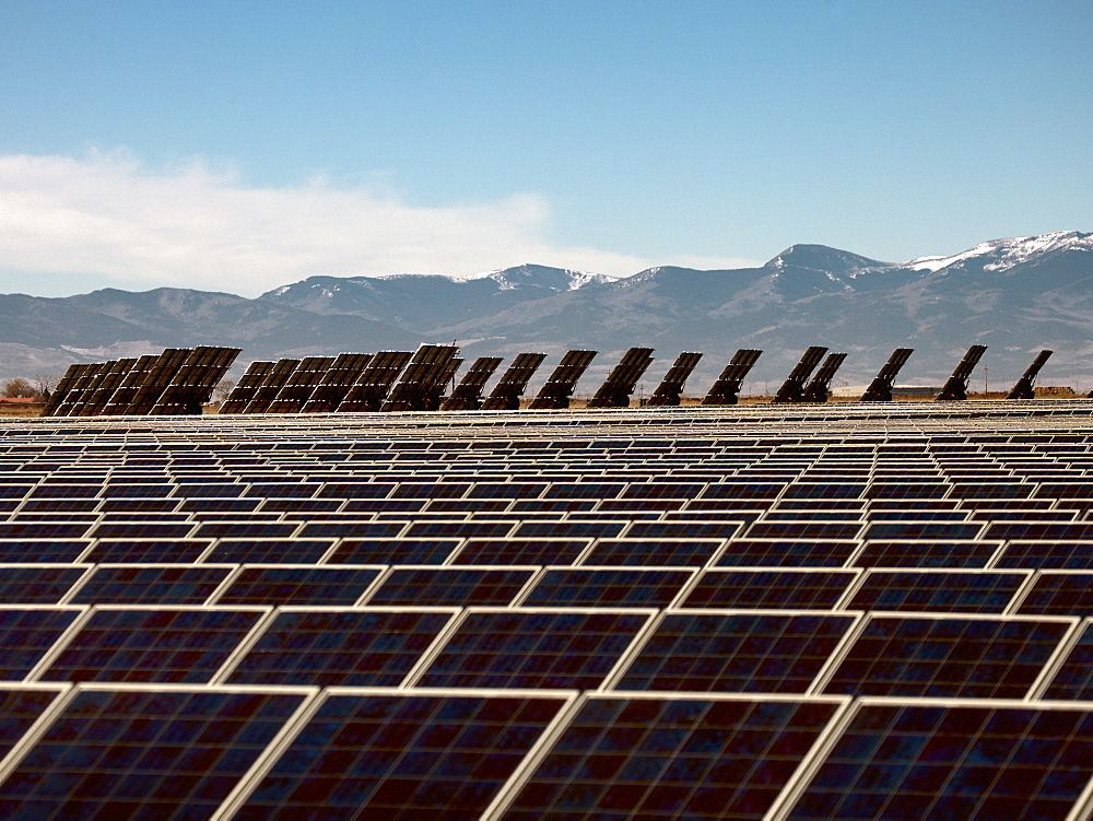 Solar panels arranged on a flat plain, some upright at an angle, and a mountain landscape beyond.