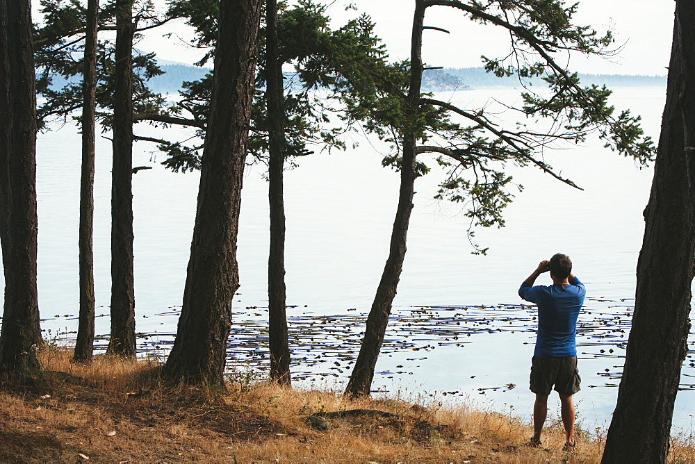 Man standing on a beach, looking through binoculars, San Juan Islands in the distance, Washington, USA.