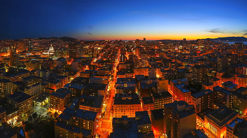 A city lit up at dusk, seen from above.