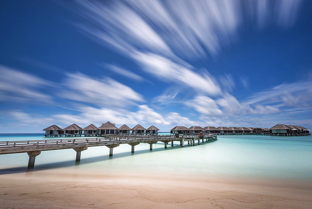 Huts along a walkway in clear ocean waters.