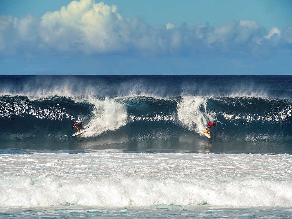 Two people surfing waves on the ocean.