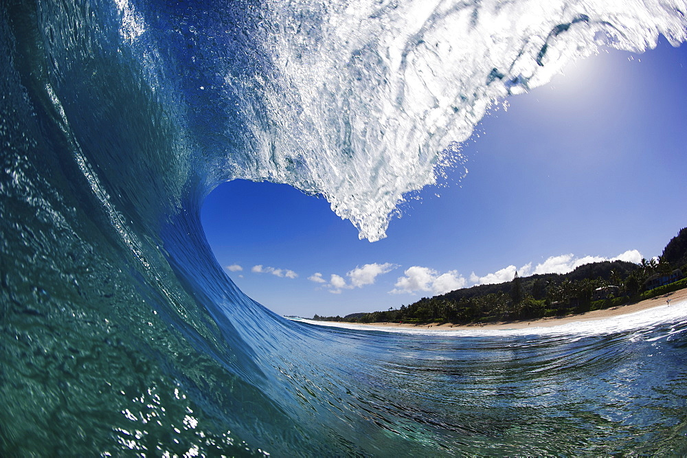A wave tunnel with curling white water against a blue sky, just offshore.