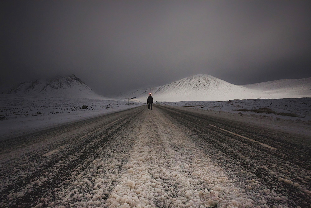 One person standing on a road in a snowy landscape.