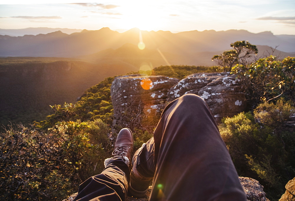 A person sitting relaxing looking at the view of sunset over a mountain range. Waist down. POV