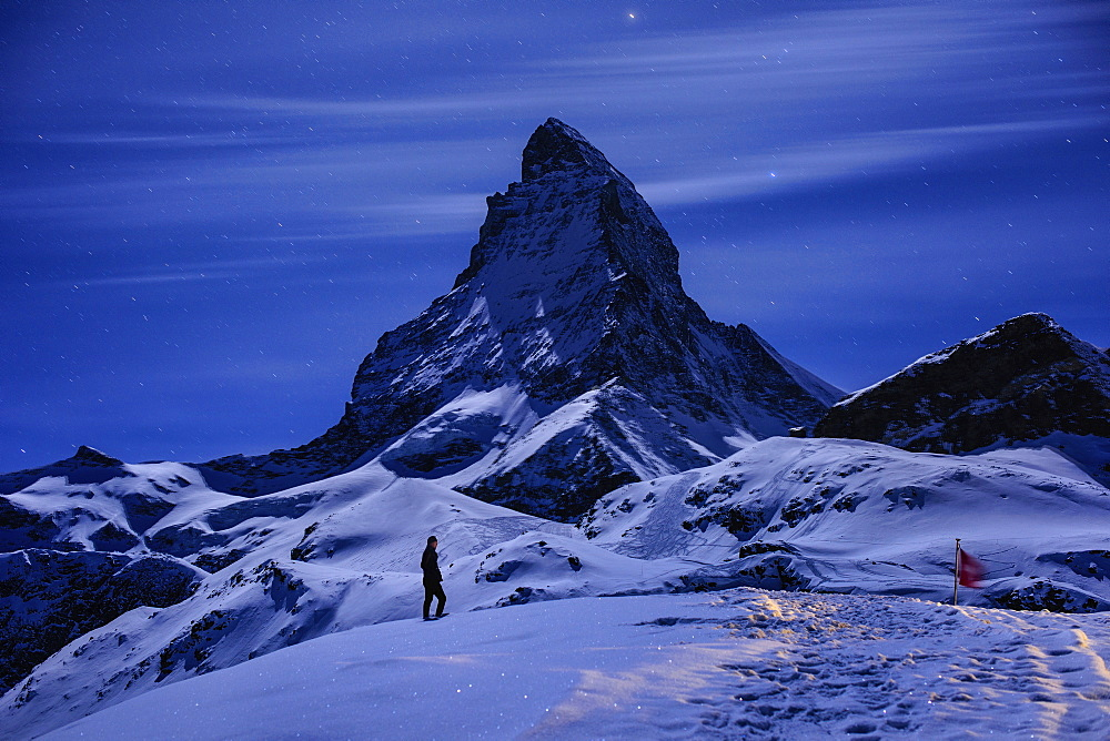 A person walking in a snowy mountainous landscape, with moonlight reflecting off the snow.  - 1174-4409