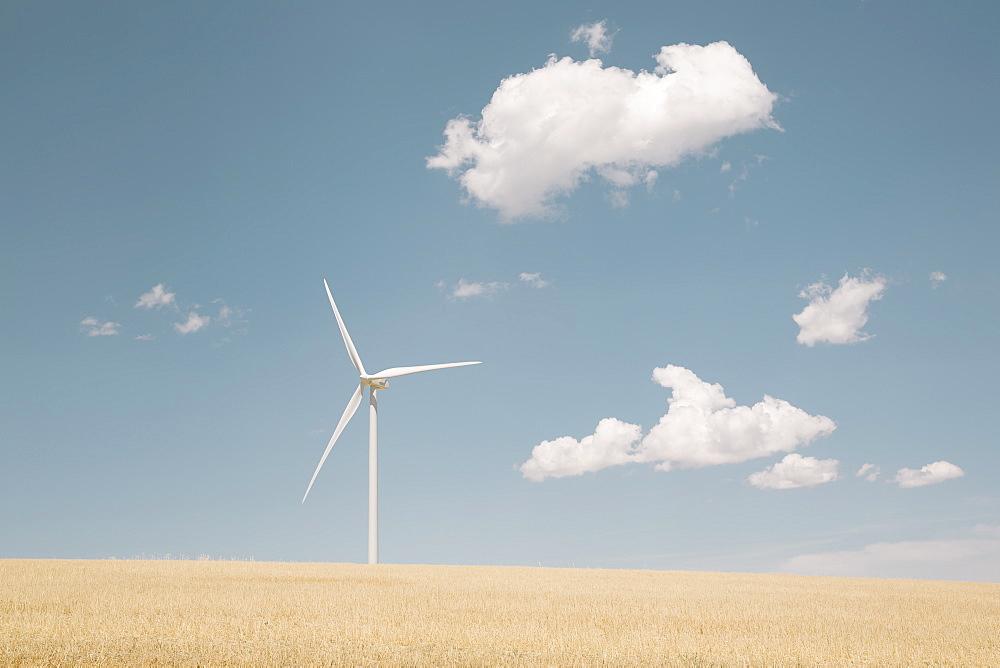 A wind turbine in a desert landscape against blue sky.