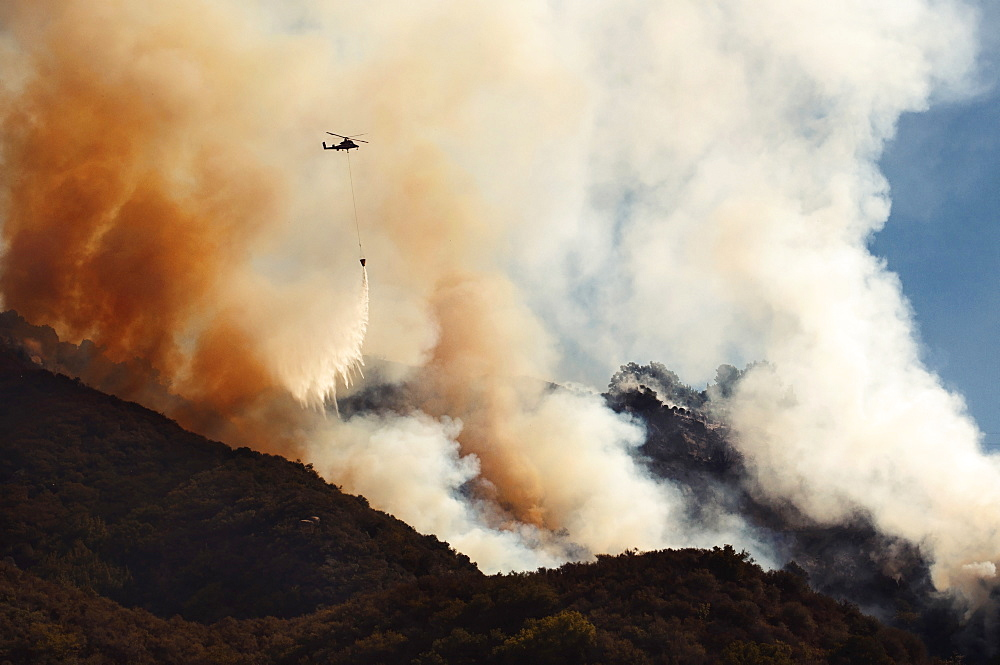 A helicopter flying over the smoke from a forest fire.