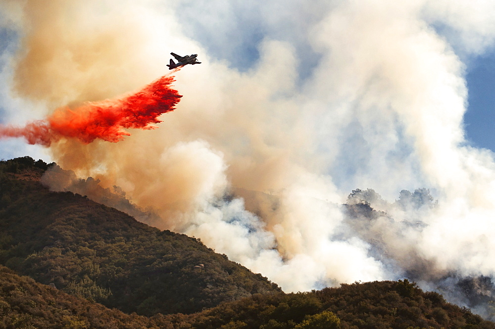 A helicopter dropping fire retardant from the air onto a forest fire. - 1174-4430