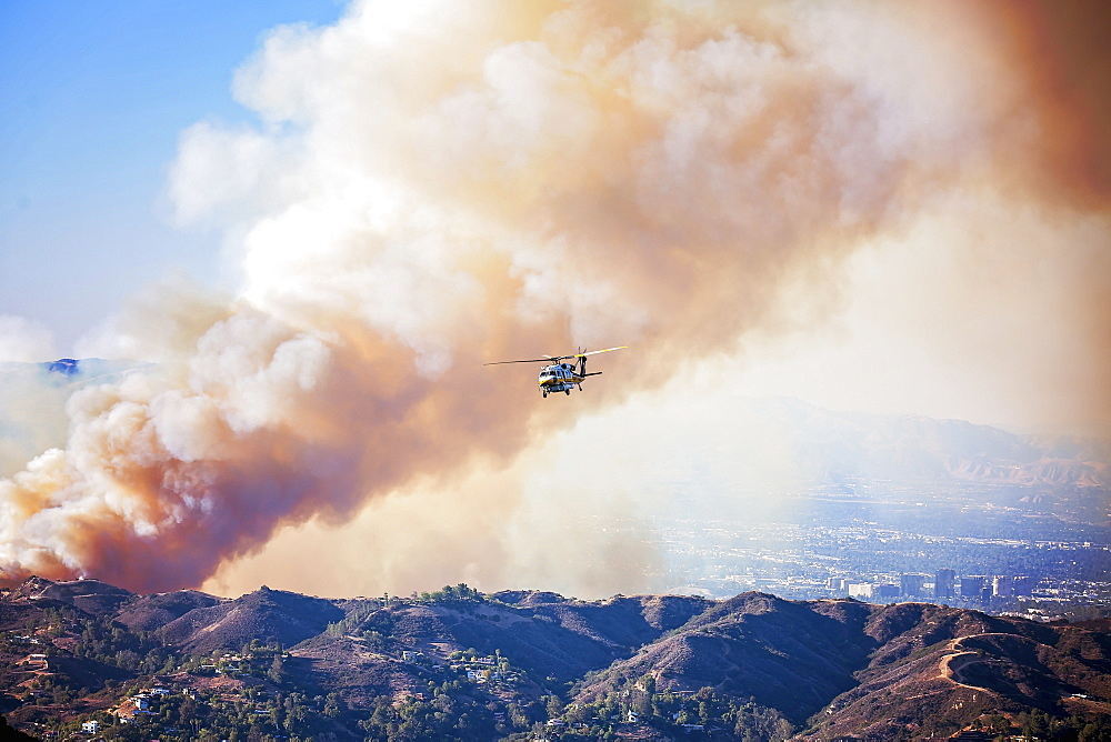 A forest fire with plumes of dense smoke in the air. A helicopter in the air.