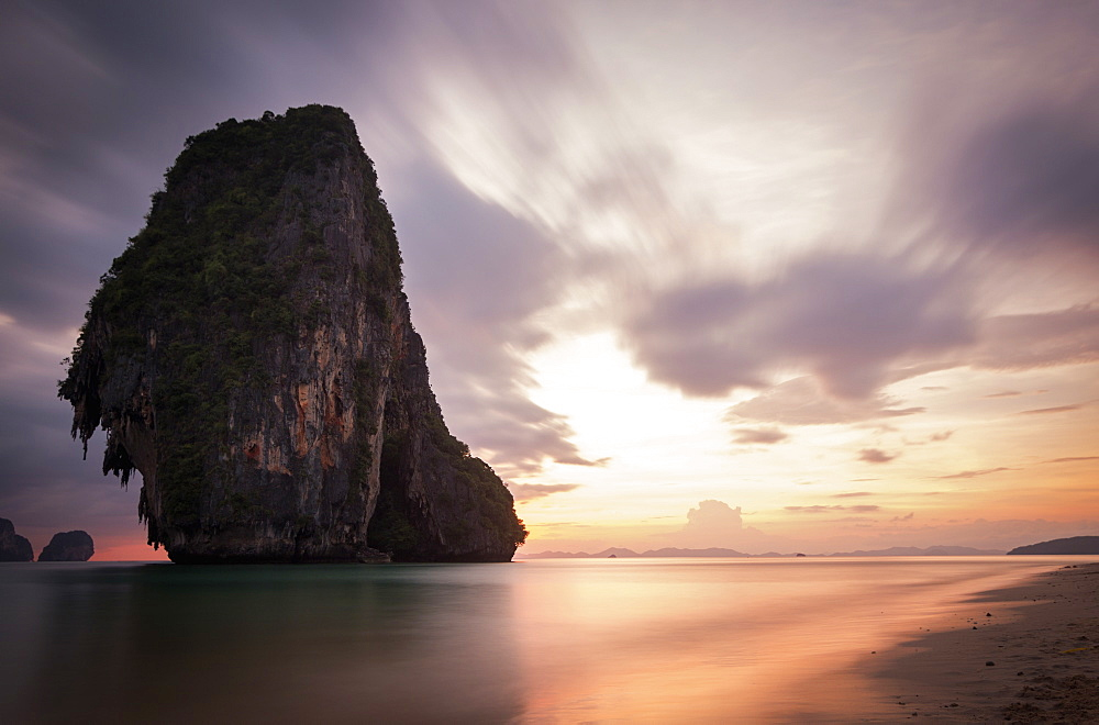 A rock formation rising out of the sea at dawn.