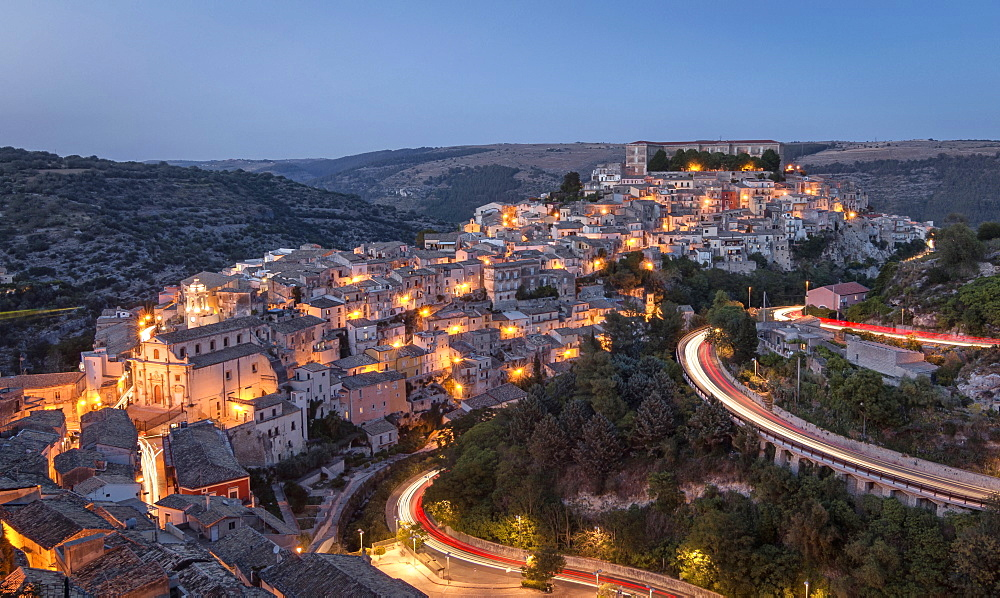 Roads running through a lit up hillside town at night.