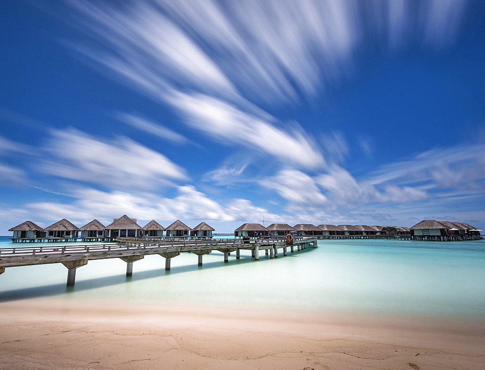 A hotel resort, small beach chalets built on stilts above shallow water  on a holiday island.