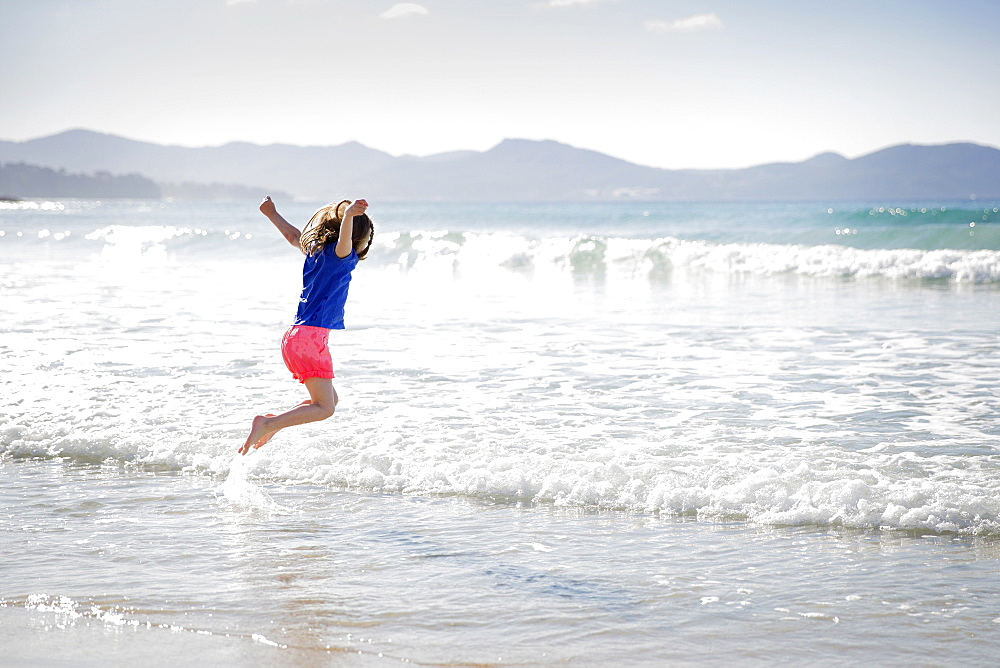 Girl wearing shorts playing on a sandy beach, jumping into a wave.