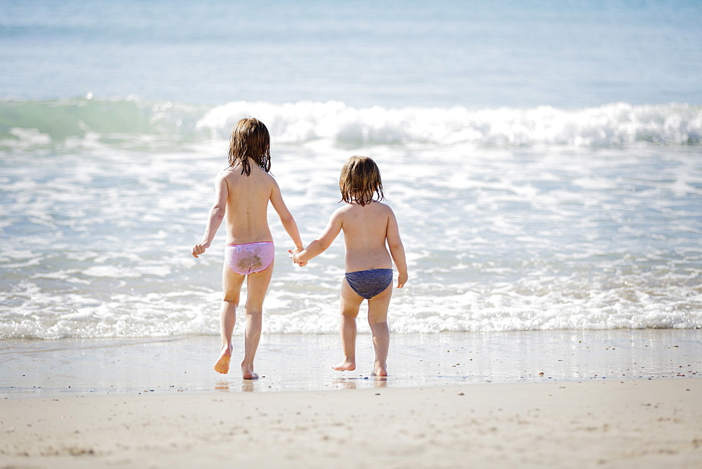 Rear view of two girls wearing underpants standing on a sandy beach, looking at ocean, holding hands.