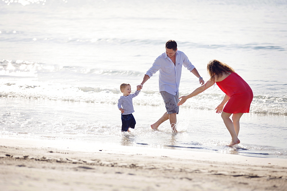 Woman wearing red dress and man wearing shorts standing on a sandy beach by the ocean, playing with young boy.