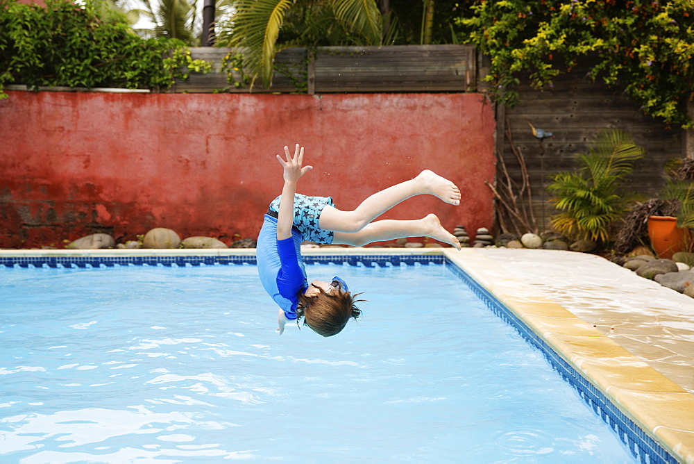 A boy in swim shorts, ten year old boy doing a back flip, a backwards somersault, into a swimming pool.