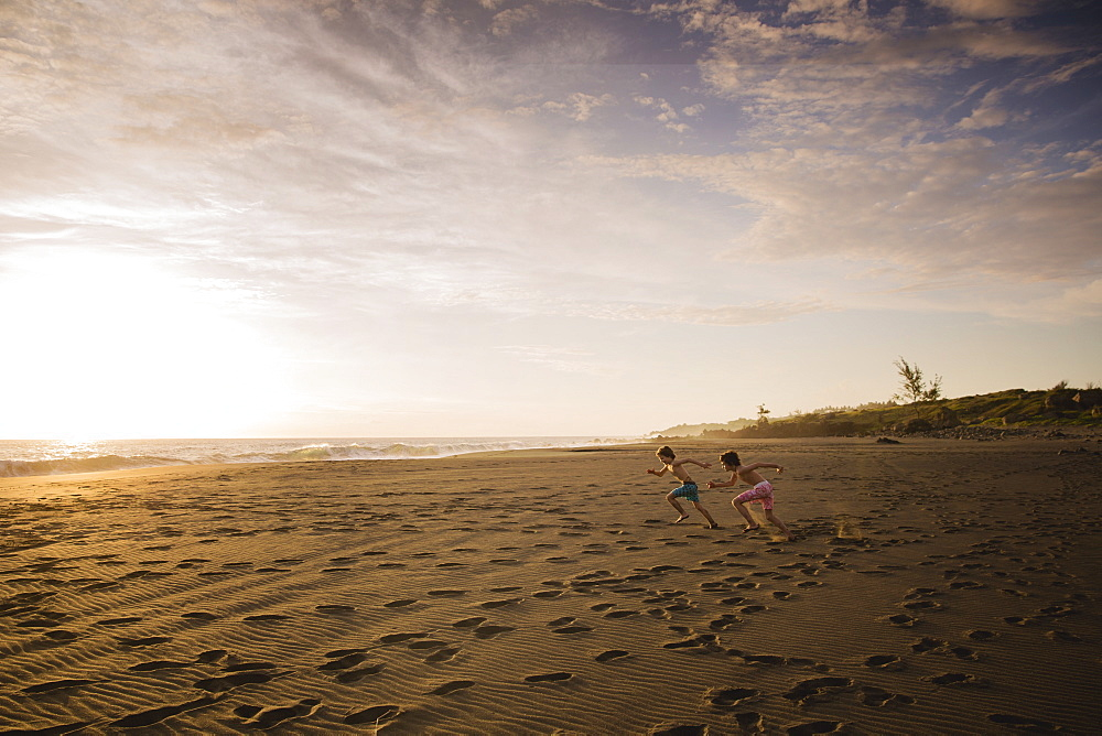 Two children running across the sand towards the sea, at sunset.