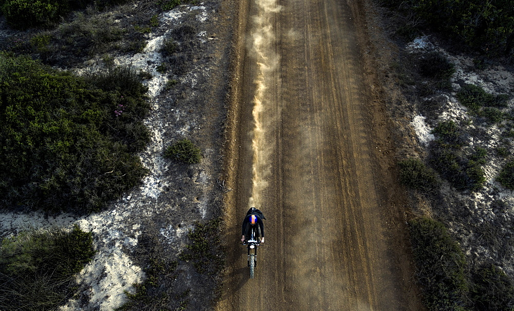 High angle view of man riding cafe racer motorcycle along dusty dirt road, United States of America