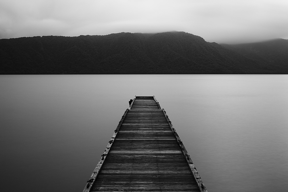 Wooden pier stretching out into the water at Towada Lake with mountains in the distance, Aomori, Japan