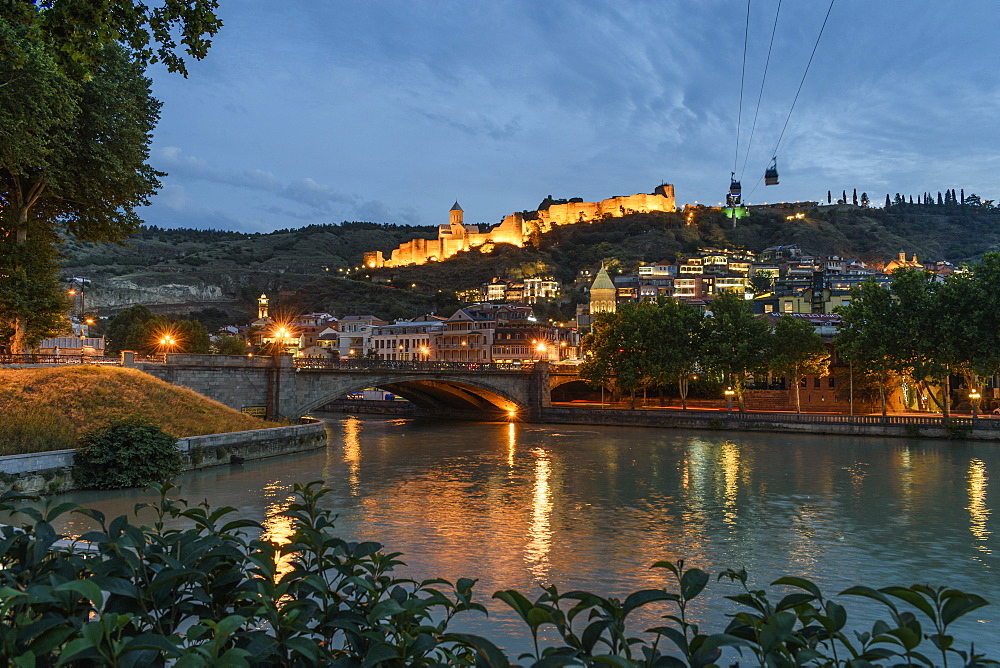 Bridge across the Kura River and illuminated fortress on hill, Tbilisi, Georgia, at sunset, Tblisi, Georgia