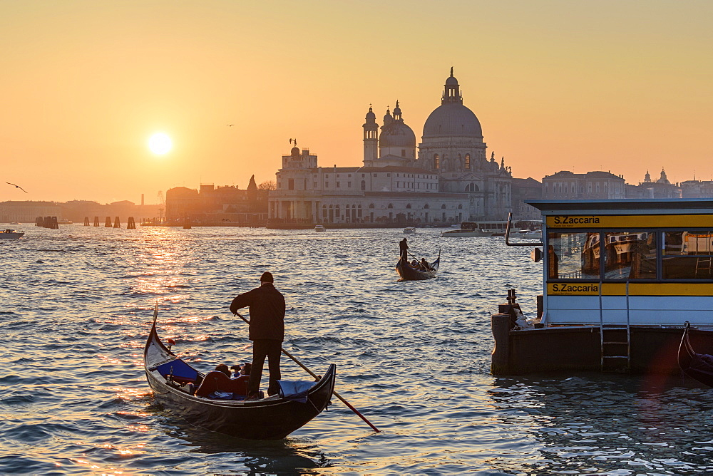 Two gondoliers on the Canale Grande in Venice, Italy, at sunrise, with the dome of Santa Maria della Salute in the distance, Venice, Italy