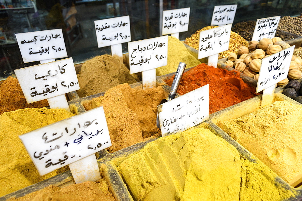 Close up of spices at a market, bright yellow and orange powders, seeds and nuts with signs, Amman, Jordan