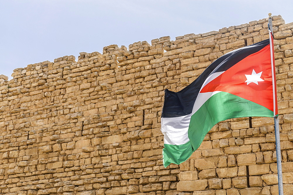 Jordanian flag flying outside stone wall of Kerak Castle, a Crusader castle in al-Karak, Kerak Castle, Jordan