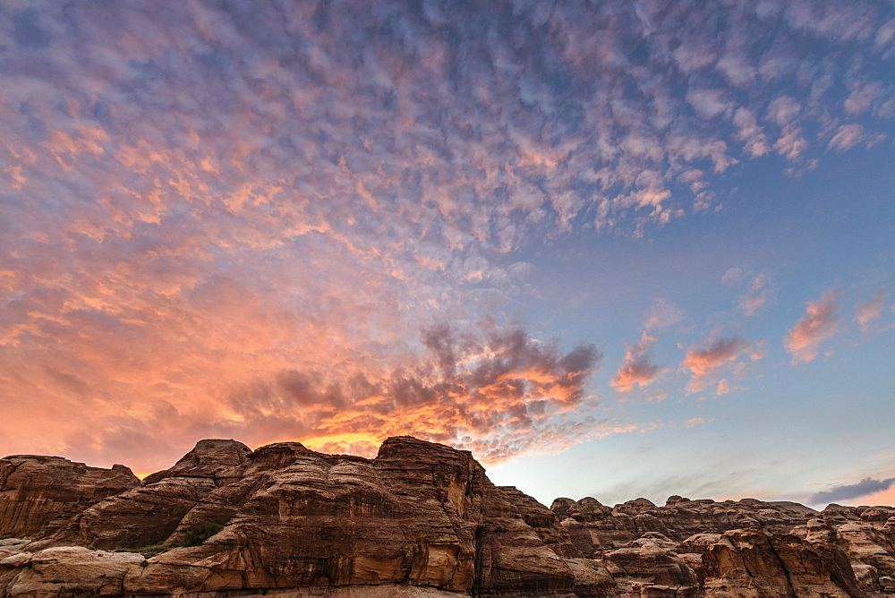 Rock formations in the Wadi Rum desert wilderness in southern Jordan at sunset, and the sun's rays reflected in light cloud, Wadi Rum, Jordan