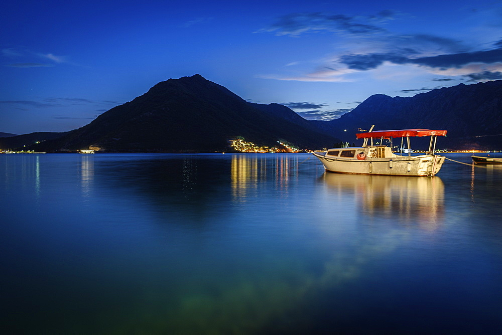 Boat moored in harbour of Perast in the Bay of Kotor, Montenegro at night, mountain in the distance, Perast, Bay of Kotor, Montenegro
